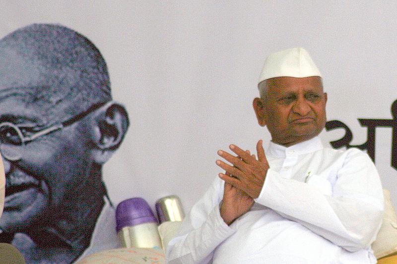 Anna Hazare sitting at a political gathering.